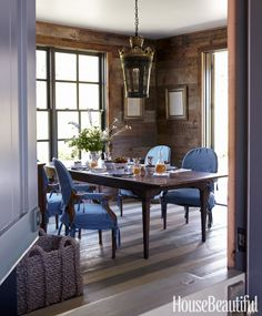"""Designer Megan Rice Yager created a cozy family gathering spot in her Sun Valley, Idaho, house. """"Those chairs were a gift from my mother-in-law, and my husband remembers them from his childhood,"""" she says. """"I needed to make them work in this context, so I had blue linen slipcovers made. Now they're more kid-friendly."""" Reproduction French farm table from Charles & Charles. Chairs slipcovered in Pindler & Pinder's Tyrone Irish linen. Hanging lamp from Lars Bolander.   - HouseBeautiful.com"""