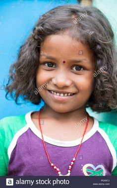 Download this stock image: PONDICHERY, PUDUCHERRY, TAMIL NADU, INDIA - SEPTEMBER CIRCA, 2017. Portrait of unidentified Indian poor kid child girl is smiling outdoor in the stree - PCKK7J from Alamy's library of millions of high resolution stock photos, illustrations and vectors.