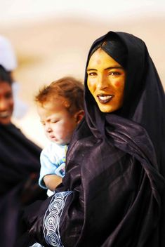 Modern Tuareg woman, with yellow ochre face paint, blueish-black lip color and eyeliner, and red circles on her cheeks and forehead.