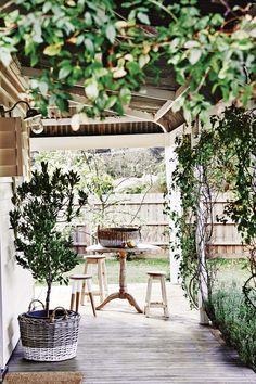 Galería rústica en una casa de fin de semana con aires de granero/cabaña. Enredadera coronando pequeña mesa de madera con banquetas.
