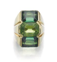 PERIDOT AND TOURMALINE RING, CIRCA 1970 Set to the centre with a cut-cornered rectangular mixed-cut peridot, flanked above and below with two step-cut tourmalines, size 531/2, French assay mark, attributed to Suzanne Belperron.