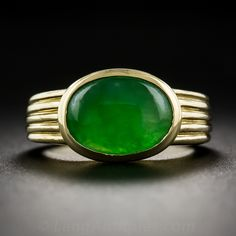 Natural Jade Ring. A bright translucent oval jadeite cabochon, with a vibrant rich green hue, is bezel-set in rich and substantial 18 karat yellow gold and is held in place by a fully fluted ring shank supported with a platinum under gallery.