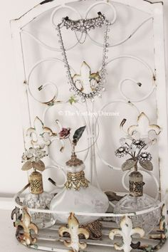 Rustic fleur de lis wrought iron piece to display vintage rhinestone perfume bottles and jewelry. ~The Vintage Dormer
