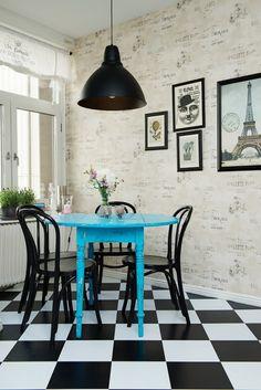 tapeta ścienna z napisami w stylu vintage,czarna lampa pendant,czarne krzesła z gietego drewna,niebieski okrągły stół i biało-czarna terakota ułożona w szachownicę w kuchni