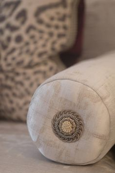 Detail of a custom bolster finished with a rosette from Samuel and Sons.