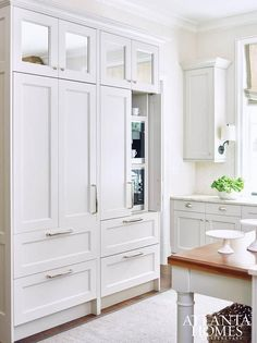 Lovely kitchen features a wall of square mirrored cabinets stacked atop pantry cabinets hiding a built in coffee machine and microwave placed next to a white paneled fridge with freezer drawers.