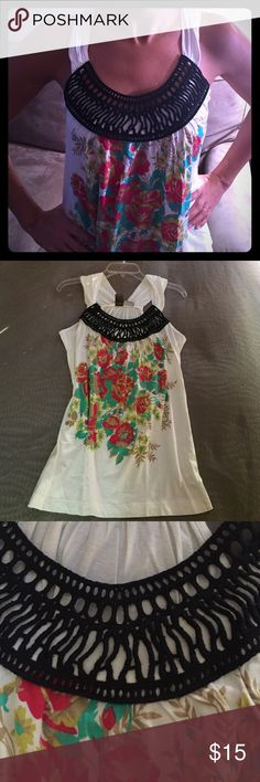 White tank top w/ colorful flowers & black weaving White cotton tank w/ colorful red, green and gold flower design. Has fun, black weaved neck design.  Great for Summer or tropical vacations.  Loose fitting, length covers backside.  Size Small (but since loose-fitting, can be worn as medium too). Worn only a few times. Lanuage Tops Tank Tops