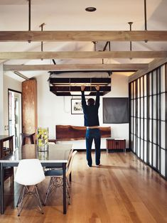 The bed was designed to hang from the ceiling and can be hoisted up and pulled down as needed. When not in use as the headboard, the large redwood slab folds down to become a desk