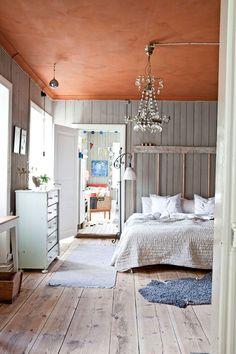 Sovrummet är målat med äggoljetempera i jordiga toner. Sänggaveln har Martin gjort själv av trä och kopparrör. Överkast, Norrgavel.