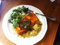 Salmon curry with tomatoes and cliantro served on a bed of quinoa and salad