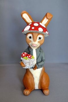 Our Woodland Rabbit has adorned himself in mushrooms, happy that spring is here! He is hand sculpted by artist Erin McSpadden out of Paperclay. He wears a large mushroom cap on his head, and holds a white basket of smaller mushrooms and moss in his paws. His jacket is painted grey and black, and his white cotton tail peeks out behind. He is hand painted with acrylic paints. Woodland Rabbit stands 9 1/2 inches tall, and is signed on the base.