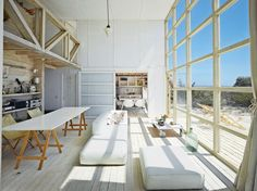 The northern facade, which faces the water, takes in the view via double-height windows in the main living room, plus terraces punched into the second floor.  Courtesy of Roland Halbe .