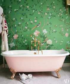 The master bath is clad in a hand-painted silk wall covering by De Gournay. Tub and fittings by C. P. Hart.