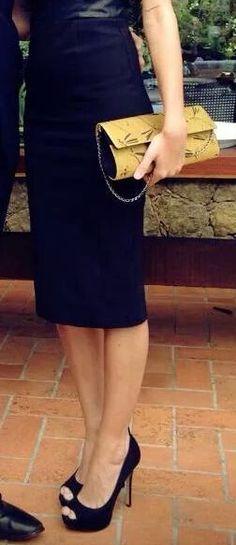 Carteira nellfernandes baguete em seda mostarda sobre vestido preto.