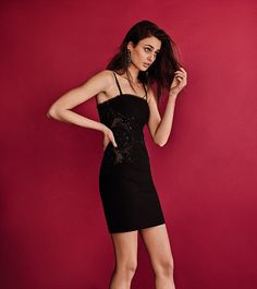 In one image, she reclines on a balcony wearing a sheer dress toughed up with a studded bl...