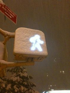 Snow man ...snow-covered WALK sign...all melted around the lit up walking man...