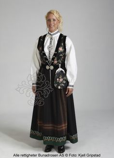 Sognebunad med sort brokadeliv og skjorte med sortsøm.