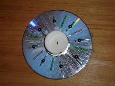 Kerstlichtje van cd. Eerst kralen rijgen. Vervolgens draad door het midden halen, weer rijgen, herhalen tot er een mooi patroon is. Tenslotte het waxinelicht er opplakken met een lijmpistool.