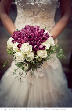Wonderful! Deep purple tulips surrounded by white roses, snowberries and vines.