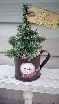 A rusty tin cup is hand painted with a whimsical snowman face, and holds a tiny tree all glittered up with mica flakes! 7 to 8 inches tall