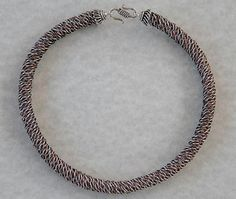 Braided Wire Necklace by Lisa Van Herik  Braid technique reasonably well explained.  No guidance on finishing the ends.