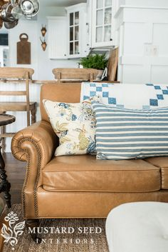 closeup of camel brown leather sofa with quilt, blue accents, white country interior, pantone butterum, light brown, caramel brown, copper brown, camel brown, copper tan, butterscotch, terra cotta, clay brown, copper