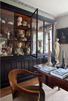 The black cabinetry makes for a bold backdrop to this collection of statuary... and oh the molding !