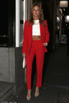 Red hot! Millie Mackintosh sizzles in a ruby trouser suit yet still shows off her bronzed abs in a crop-top beneath... after returning to London from her trip to Monaco with boyfriend Hugo Taylor