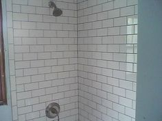 Rectified glossy white subway tile with charcoal grout for around the tub deck up to the ceiling