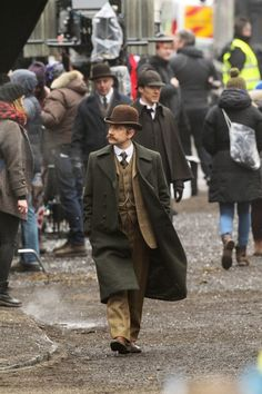 SHERLOCK (BBC) ~ Martin Freeman (John), with Benedict Cumberbatch (Sherlock) walking behind him, in Victorian costume on the Gower Street (221b Baker Street) set in London on February 7, 2015 filming the pre-Season 4 SHERLOCK: THE SPECIAL.