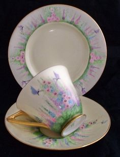 Doulton deco: unnamed tea trio signed by C. Stuart, c1946. Butterfly and hollyhocks design with gold gilt highlights and trim.