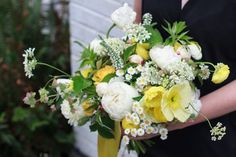 Spring wedding bridal bouquet by Bleedfoot Florals. White and yellow peonies Icelandic poppies, oregano, queen annes lace, raspberry, chamomile, ranunculus. Fresh happy yellow brides color scheme, yellow silk ribbons, loose and garden style.