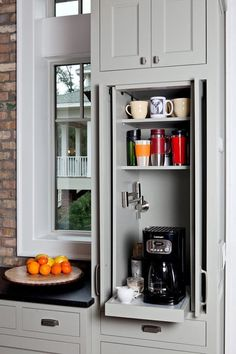 """Breakfast bars, or separate """"morning areas,"""" are coveted details in kitchens with room to spare. In smaller kitchens, hideaway features, like this tabletop, are incredibly useful. What about combining the two features and creating a hideaway breakfast area—in this case, a roll-out cabinet dedicated to your morning joe, complete with pot-filler faucet!"""