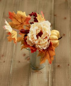 Seasonal fall floral accent piece. Simple statement that includes a lot of our favorite parts of fall decorating. This arrangement includes: - Mini Yellow Pumpkin - Yellow and Orange Fall Maple Leaves