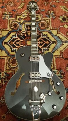 """The Emperor Swingster is a dazzling go-to rockabilly, jazz and rock hollowbody classic. It features Epiphone SwingBucker™ pickups with classic Alnico-V magnets, Grover® machine heads, a LockTone™ Tune-o-matic bridge, and best of all, a licensed B30 Bigsby® with original style """"wire"""" handle as preferred by """"Certified Guitar Player"""" and legend Chet Atkins.Starting with the same body and neck as used on their Emperor-II guitar and made famous by the jazz master himself, Joe ..."""