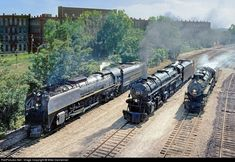 Three steam locomotives simmer on a hot, humid late spring afternoon at St. Louis, Missouri, on June 13, 1990, in a gathering to celebrate Trains Magazine's 50th anniversary. Union Pacific 4-8-4 No. 844, Norfolk and Western 2-6-6-4 No. 1218 and and Frisco 4-8-2 No. 1522 pose at Burlington Northern's (former Frisco) Chouteau Yard during the National Railway Historical Society's National Convention festivities.