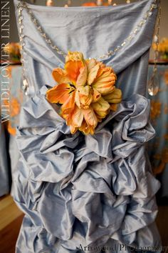A stunning combination of a ruffled wedding chair cover and a delightful large flower with a touch of bling!