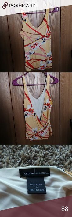 Moda International wrap back floral tank Front is a v neck, back is a low cut wrap style.  Base color is a cream orange.  Accents are red, brown, and pink.  Flowers are white with red, yellow, and blue accents.   Tag says dry clean only, but I've washed on the gentle cycle and hung to dry with no issue thus far.  100% rayon. Will show bra band, but would be cute with a bralette (or swim suit.) On a non petite this will probably be crop length. Moda International Tops Tank Tops