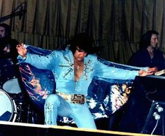 At the end of a concert Elvis is exhausted, so he kneels on one knee and spreads his cape out. People kept telling him that they loved him and by spreading out the cape he was returning his love to them.