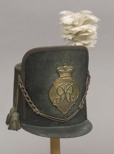 "British Infantry Officer's Shako 1812-1816 The cylindrical body and false front retaining much original nap, original unbound front peak, correct pattern festoons and double bullions in gold metal and crimson silk lace. Original proofed linings and leather sweat band, the crown lining with trade label, ""Tomlinson Hatter Back Of The Inns Norwich"", the frontal plate in copper gilt of standard crowned rococo pattern and bearing the large ""GR"" cypher only."