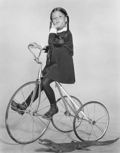 Wednesday Adams rides tricycle with baby alligator