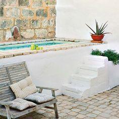 En la isla de Menorca, con suelo de barro, viguería vista y paredes blancas, se encuentra esta vivienda, ubicada en unos viejos establos rehabilitados.