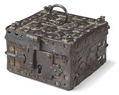 A SPANISH IRON-MOUNTED WOOD CASKET 15TH CENTURY The hinged lid with a loop handle, hasp and four horse-head terminals to the corners; the box decorated overall with floral motifs; minor wear