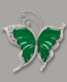 JADEITE AND DIAMOND 'BUTTERFLY' BROOCH Modelled as a butterfly, the wings set with carved jadeite plaque of translucent emerald green colour, embellished by circular-cut diamonds together weighing approximately 1.40 carats, mounted in 18 karat white gold, with pendant loop fitting.