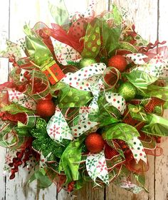 Deco Mesh Christmas Wreath and Xmas Door Wreaths are a great way to make your home festive and add color to your front door to any room in your house! This wreath is a fabulous way to make your house feel warm and welcoming for family and friends. This Mesh Christmas Wreath features lime green and red ball ornaments. A pretty glittered lime green poinsettia is nestled on the lower right side. Lots of glitter and sparkle Four Gorgeous ribbon streamers were used, 2 sheer lime with glitter…