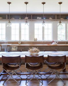 Farmhouse table, mid-century leather directors chairs, wall of windows, display cabinet above  | Ben Watts's Montauk Home