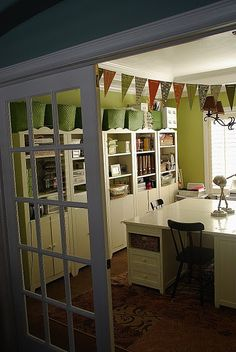 Craft/Office space. I like the clean white, contrast in wall color, the large desk in the middle and combination of open/closed storage space. Dining turned office is the perfect location b/c it's close to the kitchen and would make a great homework space for the kids. Probably need more countertop space or a computer nook.