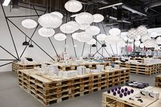 What's particularly interesting about pop-up is the challenge to create an impact with less budget and time to set up. The paper lanterns are very inexpensive and as we can see in the picture, they create a beautiful contrast against the rigid and square aesthetic of wooden pallets used as tables. Look closer towards the back and you will see a simple linear design on the wall that breaks the tables rigidness with random angled movements.  #interior #design #retail #pop-up