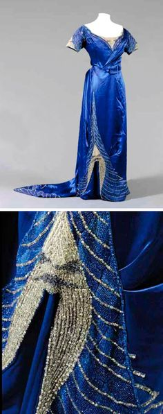 Evening gown, Worth, ca. 1907. Royal blue satin with blue beads rhinestones at bodice front. Sleeves kick pleat at skirt front with assymetrical tulip panel. Beading follows line of hem to slightly trained skirt. Sotheby's