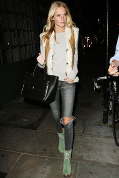 Poppy Delevingne was spotted after a night out as she left the Groucho club on August 15th in London where she spent time with friends Sienna Miller and designer Matthew Williamson. Delevingne's wore ripped grey skinny jeans, a long sleeve seater, and a fur and suede vest, and long with pistachio boots and black handbag.